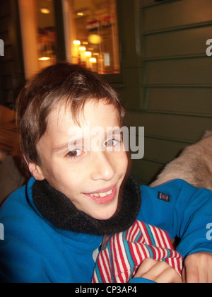 Young boy smiling at camera. posing leaning at the table, looking happy,  Stockholm, Sweden - Stock Photo