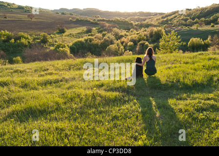 A beautiful young woman hugs her dog as they sit in a field watching the sunset in the countryside - Stock Photo