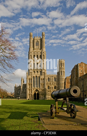 The west Tower and entrance to Ely Cathedral Cambridgeshire England with Russian cannon on Palace Green in foreground - Stock Photo