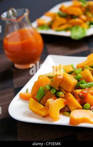 Table with two plates of sweet potato apricot salad with green beans and pistachios and an apricot vinaigrette. - Stock Photo