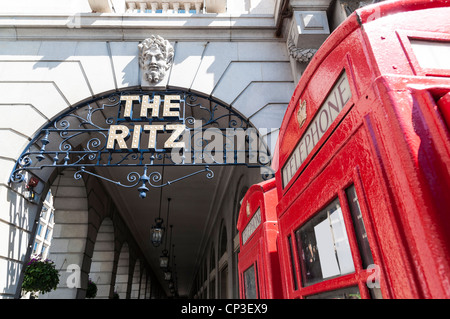 LONDON, UK - APRIL 30: Details of the Ritz hotel entrance, with red phone booth. April 30, 2012 in London. The luxury - Stock Photo