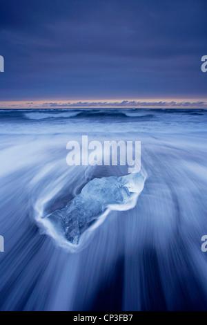 Iceberg washing up on the black volcanic beach at Jokulsarlon in Iceland - Stock Photo