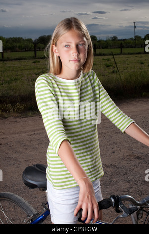 Eleven year old girl on her bike on dirt road. - Stock Photo