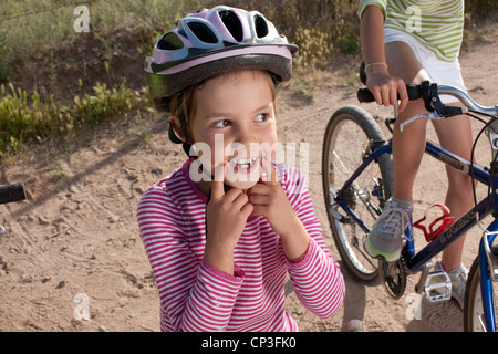 Six year old girl forcing a smile with her fingers, wearing a helmet. - Stock Photo