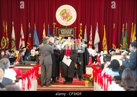 Male student receiving diploma at college graduation - Stock Photo