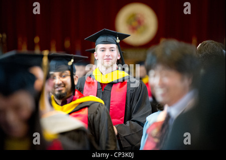 Male college graduate amongst crowd of classmates at ceremony - Stock Photo