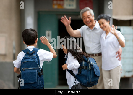 Chinese schoolkids with grandparents waving - Stock Photo