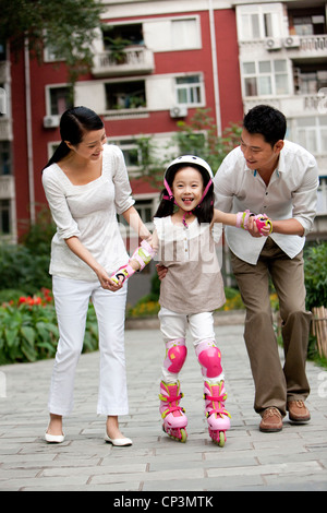 Chinese family with daughter in rollerblades - Stock Photo