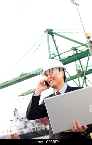 businessman using a laptop and mobile phone at a shipping port - Stock Photo