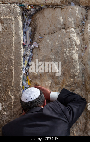 Jewish man prays next to a crack filled with letters containing written prayers at the Western Wall in Jerusalem. - Stock Photo