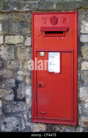 An old red letter box embedded into a stone wall - Stock Photo
