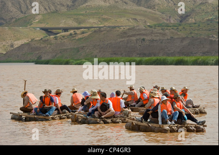 Chinese tourists travel along the Yellow River on traditional sheepskin rafts - one of the 'rides' at the Shapatou - Stock Photo
