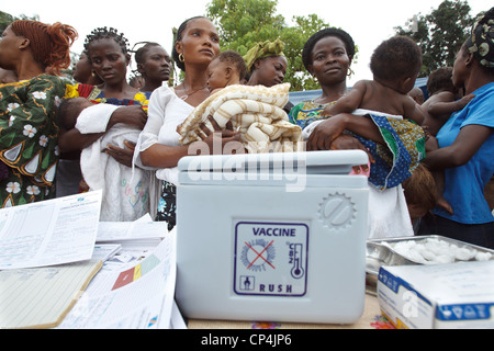 Mothers wait to have their children vaccinated during routine vaccination at the Nyunzu health center in the town - Stock Photo