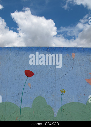 painted mural on wall in playground park with blue sky and clouds - Stock Photo