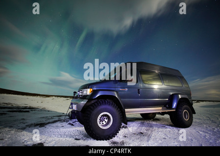Super off road jeep 4x4 under the Northern Lights on the edge of Jokulsarlon lagoon in Iceland - Stock Photo