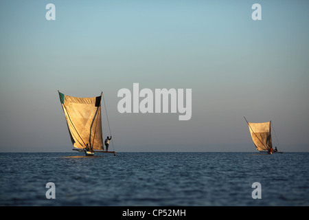 Two outrigger canoes sailing at sunrise at Belo-Sur-Mer, Western Madagascar, Africa - Stock Photo