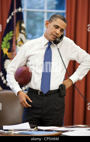 President Barack Obama talks on the phone with House Speaker John Boehner in the Oval Office, April 8, 2011. - Stock Photo