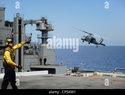 Aviation Boatswain's Mate (Handling) 2nd Class Michael Edwards signals to an MH-60S Sea Hawk helicopter assigned - Stock Photo