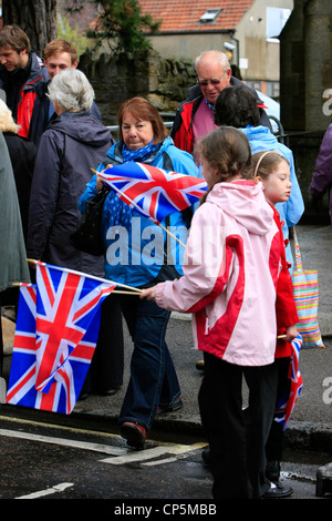 Royalist supporters carrying flags to wave at the Queen on her visit to Sherborne in Dorset - Stock Photo