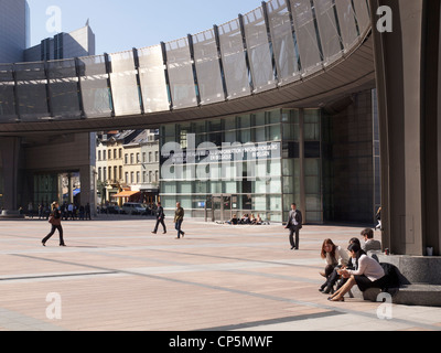 People sitting in the sun at lunchtime, European Parliament buildings, Brussels, Belgium - Stock Photo