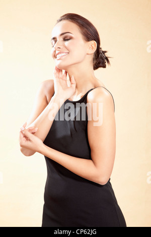 Young woman in black dress, smiling - Stock Photo