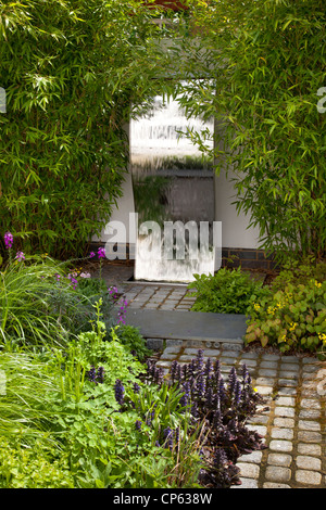 steel wall water feature in modern contemporary enclosed english garden - Stock Photo