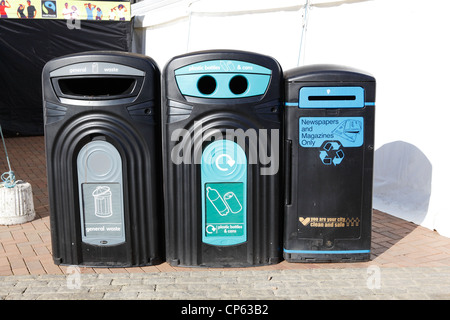 Three large recycling bins side by side. To recycle cans.plastic bottles.newspapers and magazines. In a public place. - Stock Photo