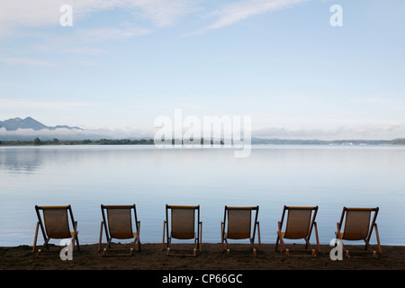 Germany, Bavaria, Chiemsee, Row of folded chairs by lake - Stock Photo