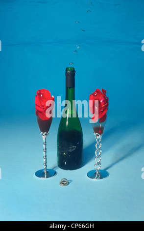 Bottle of red wine and glasses under water in a pool - Stock Photo