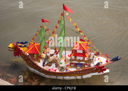 A replica miniature model boat, laden with religious offerings to the Sea Goddess, on Thu Bon River, Hoi An, Vietnam - Stock Photo