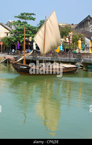 Vertical view of a traditional Vietnamese fishing boat with it's sail up moored near the bascule Thu Bồn River bridge - Stock Photo