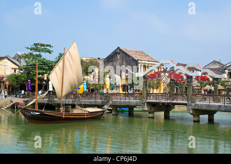 Horizontal view of traditional Vietnamese fishing boat with it's sail up moored near the bascule Thu Bồn River bridge - Stock Photo