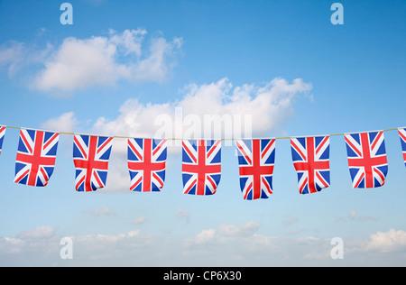 Union Jack bunting against blue sky - Stock Photo