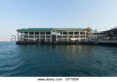The new Star Ferry terminal on Hong Kong island with quiet sea and setting sun - Stock Photo
