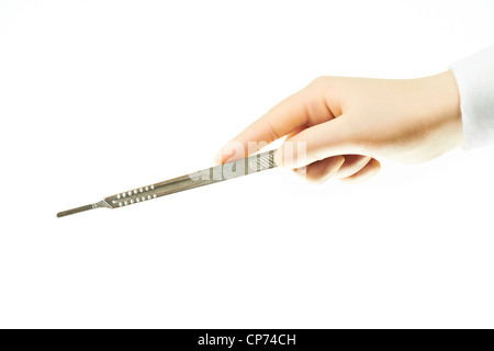 Surgical instrument (scalpel handle) held by surgeons hand - Stock Photo