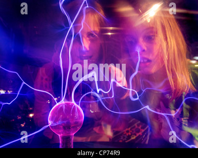 Girls 11 and 7 years old fascinated by tesla plasma ball, Tegelen, the Netherlands - Stock Photo