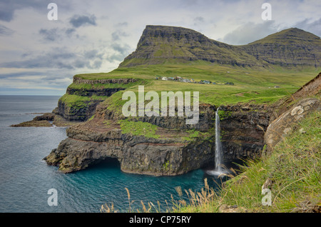 The village 'Gasadalur' is surrounded by high mountains and the clear blue Atlantic on the island 'Vagar'. - Stock Photo