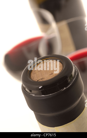 Bottle of red wine with black foil cut off and two wine glasses at background. (Shallow DOF) - Stock Photo