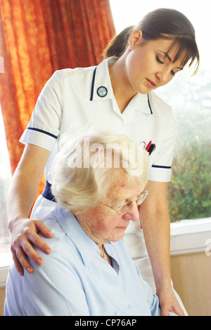 District nurse giving advice on home visit - Stock Photo