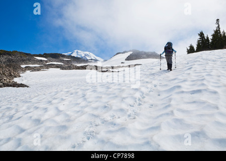 A woman wearing a backpack hiking up a steep snow field in Mount Rainier National Park, Washington, USA. - Stock Photo