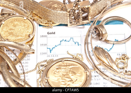 Old jewelry and gold coins with printed gold chart in background - Stock Photo