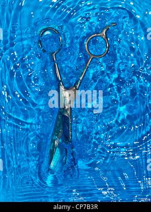 barber scissors under water - Stock Photo
