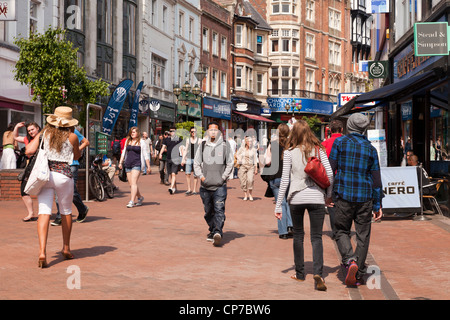 A busy scene in Old Christchurch Road, one of Bournemouth's main shopping streets, with crowds of people walking. - Stock Photo