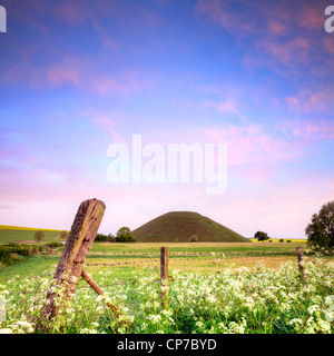 Silbury Hill, a Neolithic monument in Wiltshire, nearAvebury, on a beautiful spring morning with blue sky and pink - Stock Photo