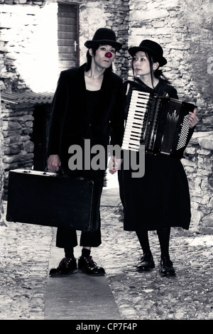 a couple of clowns is walking through an old, narrow street, the man has an old suitcase, the woman plays the accordion - Stock Photo