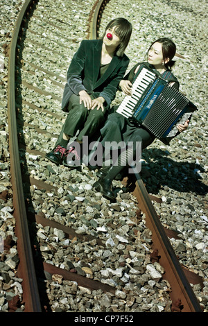 a sad clown couple sitting on railroad tracks - the woman plays the accordion - Stock Photo