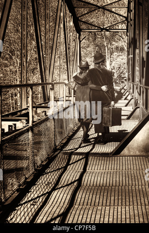 a vagabond couple goes to an old suitcase on an old railway bridge - Stock Photo