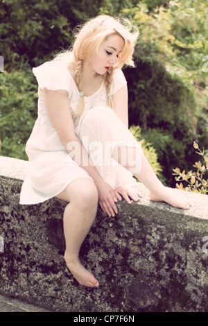 young woman with braids sitting on a wall in a white dress - Stock Photo