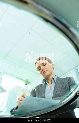 Vertical shot of business woman viewed from below the glassy table - Stock Photo