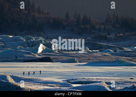 Family of ice skaters near Sheridan Glacier with icebergs in the background, Cordova, Southcentral Alaska, Winter - Stock Photo